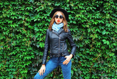 Fashion young woman model wearing black rock jacket, hat posing over green leaves Stock Photos