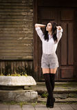Fashion young woman posing near a old wooden wall. Royalty Free Stock Images