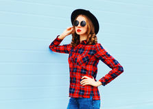 Fashion young woman posing wearing black hat, red checkered shirt over blue background Stock Images