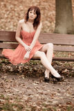 Fashion young woman in red dress relaxing in park on bench Stock Photo