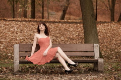 Fashion young woman in red dress relaxing in park on bench Royalty Free Stock Photography