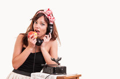 Fashion young woman with a retro look speaks at a vintage phone Stock Images