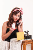 Fashion young woman with a retro look speaks at a vintage phone Stock Photos