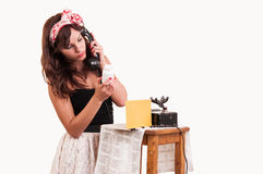 Fashion young woman with a retro look speaks at a vintage phone Stock Photo