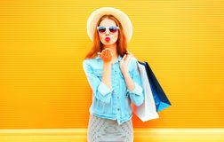 Fashion young woman sends an air kiss holds a shopping bags in straw hat Stock Images