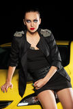 Fashion young woman sitting on a car in the night Royalty Free Stock Images