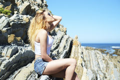 Fashion young woman sitting on sea rocks. Young woman sitting on sea rocks Stock Photo