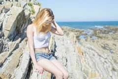Fashion young woman sitting on sea rocks. Young woman sitting on sea rocks Royalty Free Stock Images