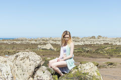Fashion young woman sitting on sea rocks. Young woman sitting on sea rocks Royalty Free Stock Photography
