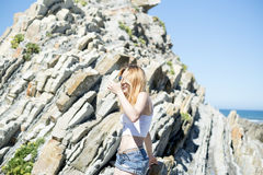 Fashion young woman sitting on sea rocks. Fashion happiness young woman sitting on sea rocks Stock Images
