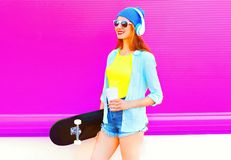 Fashion young woman with skateboard and coffee cup listens to music. On pink background Stock Photography