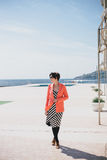 Fashion young woman standing on a embankment Royalty Free Stock Images