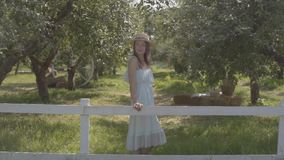 Fashion young woman in straw hat and long white dress standing in the green summer garden behind the fence. Rural. Cute young woman in straw hat and long white stock video