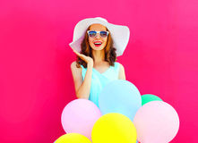 Fashion young woman is surprised with an air colorful balloons is having fun on pink background Stock Photos