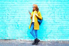Fashion young woman using smartphone on blue brick background Royalty Free Stock Photo