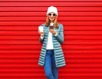 Fashion young woman is using smartphone with coffee cup on red Stock Images