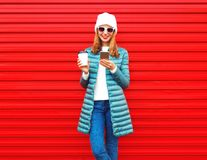 Fashion young woman is using smartphone with coffee cup on red. Fashion young woman is using smartphone with coffee cup on a red background in the city Stock Image