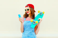 Fashion young woman is using smartphone and holds skateboard over white Stock Photos