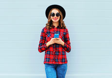 Fashion young woman using smartphone outdoors in city, wearing black hat red checkered shirt Stock Photo