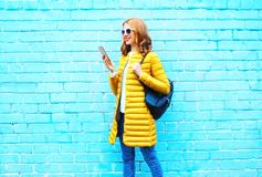 Fashion young woman is using smartphone walks over a blue brick Royalty Free Stock Image