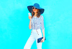 Fashion young woman is using a smartphone wearing a straw hat, white pants with a handbag clutch over colorful blue Stock Photography