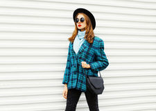 Fashion young woman wearing black hat checkered coat jacket handbag walking in city over white Royalty Free Stock Images