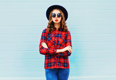 Fashion young woman wearing a black hat, red checkered shirt over blue. Background Stock Image
