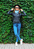 Fashion young woman wearing a black rock jacket, handbag over green leaves wall. Fashion young woman wearing a black rock jacket, handbag over green leaves Stock Photo