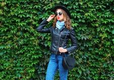 Fashion young woman wearing a black rock jacket, handbag posing over green leaves wall. Fashion young woman wearing a black rock jacket, handbag posing over Stock Photo