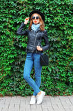 Fashion young woman wearing black rock jacket, hat and bag over green leaves wall. Fashion young woman wearing black rock jacket, hat and bag over green leaves Stock Photo