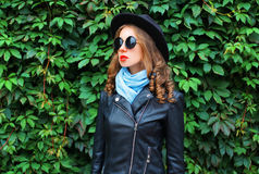 Fashion young woman wearing black rock jacket, hat over green leaves texture wall. Profile view Royalty Free Stock Photo