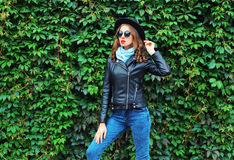 Fashion young woman wearing a black rock jacket, hat posing over green leaves. Wall Royalty Free Stock Image