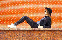 Fashion young woman wearing a black rock style lying over bricks background Stock Photo