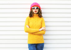 Fashion young woman wearing knitted pink hat, yellow colorful sweater over white. Background Royalty Free Stock Image