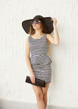 Fashion young woman wearing a striped dress and straw hat Royalty Free Stock Photography