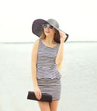 Fashion young woman wearing a striped dress and straw hat Stock Photo