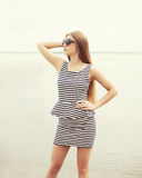 Fashion young woman wearing a sunglasses and striped dress Stock Image