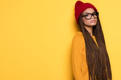 Fashionable african american girl. Fashionable young african american girl wearing red cap posing on yellow background Royalty Free Stock Images
