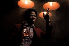 fashionable african american man in hat gesturing smoking cigar and drinking cognac in dark room stock photos