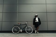 Fashionable african american man wearing fedora hat using smartphone while standing. By his bicycle stock photography