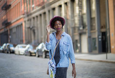 Fashionable African American woman walking and listening to musi Royalty Free Stock Photography