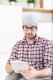 Fashionable architect or executive holding tablet device at his office stock photography