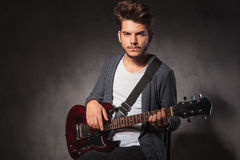 Fashionable artist playing guitar in dark studio background Stock Photo