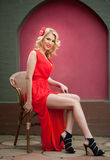 Fashionable attractive blonde woman in red dress sitting on chair. Beautiful elegant woman  with red scarf posing in elegant scene Royalty Free Stock Image