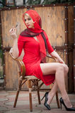 Fashionable attractive blonde woman in red dress sitting on chair. Beautiful elegant woman  with red scarf posing in elegant scene. Ry .Sensual gorgeous young Stock Photo