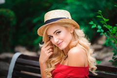 Fashionable attractive blonde woman in red dress sitting on chair royalty free stock photo