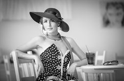 Fashionable attractive lady with hat and scarf sitting in restaurant. Indoor shot. Young woman posing in elegant scenery, black and white. Art photo of elegant Royalty Free Stock Photos