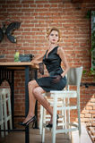 Fashionable attractive lady with little black dress and gloves sitting on chair in restaurant having a drink on the table Royalty Free Stock Photography