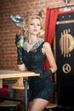 Fashionable attractive lady with little black dress and long gloves standing near a restaurant table having a drink Stock Image