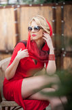 Fashionable attractive lady with red dress and headscarf sitting on chair in restaurant, outdoor shot in sunny day. Stock Images